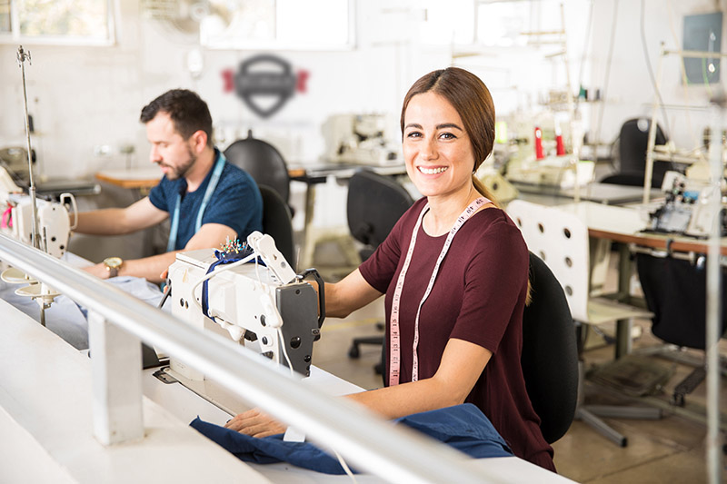Portrait of a beautiful young Hispanic woman working as a tailor in a textile factory and smiling